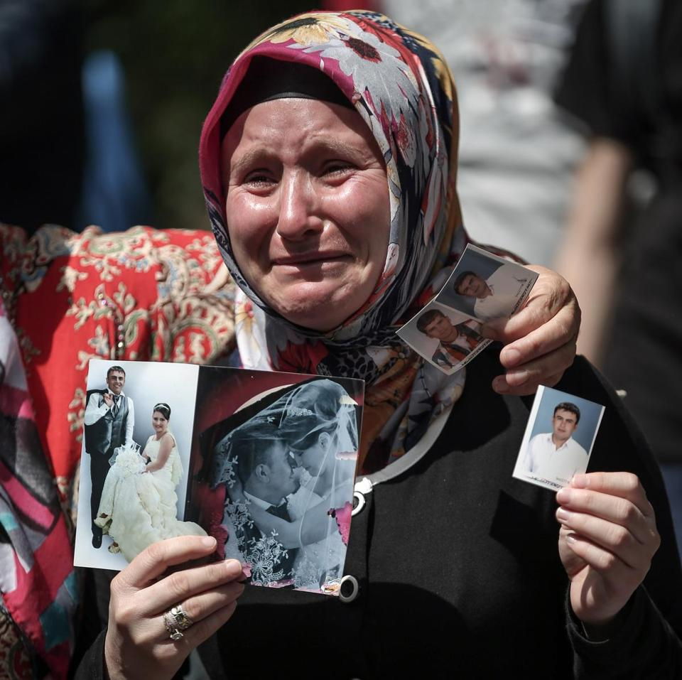 A woman in Soma, Turkey, displayed pictures Thursday of her son, a victim of a mine accident that killed hundreds.