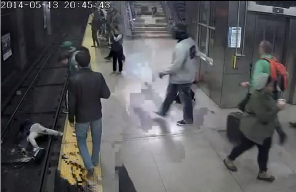 A still from MBTA security footage shows a woman falling off the platform in Back Bay station.
