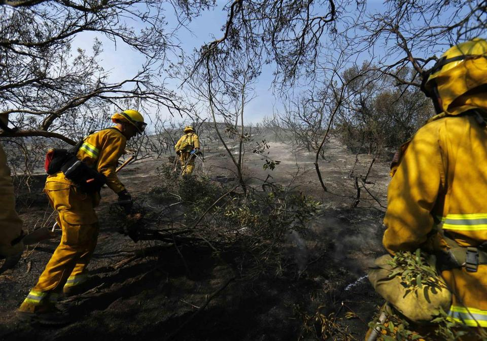 Firefighters helped clear brush and put out hot spots from one of 10 fires in San Diego County.