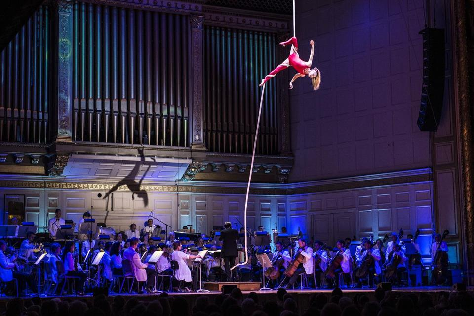 An aerialist from Cirque de la Symphonie performs above the Symphony Hall stage as the Pops play below Friday night.