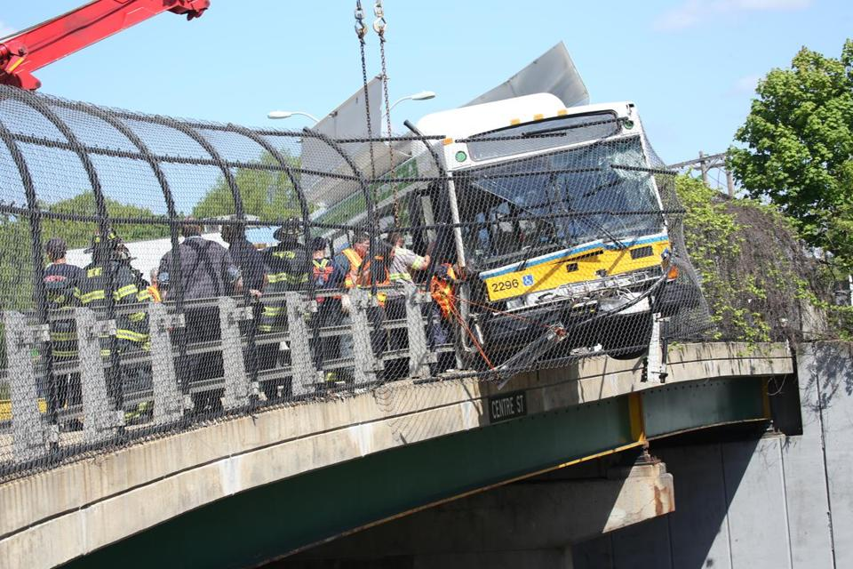 An MBTA bus hung over an overpass.