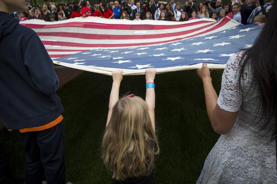 A child helped hold aloft the National 9/11 Flag, donated by the New York Says Thank You Foundation, on the grounds of the 9/11 Memorial Plaza before the flag was placed in the National Sept. 11 Memorial Museum in New York Wednesday. Reactions were mixed as the museum opened to the public.