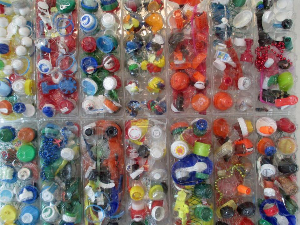 "Colorful piece: Egg cartons as art: Sinikka Nogelo is working on a ""Kitchen Egg"" wall, filling egg containers with trash and painting them, to make a comment about the environment. (Diane Bair for The Boston Globe)"