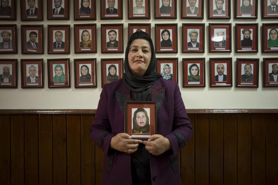 Afghan lawmaker Samia Azizi Sadat holds her picture, which hangs on the wall among pictures of Afghanistan's 249 parliamentarians, in Kabul in March.
