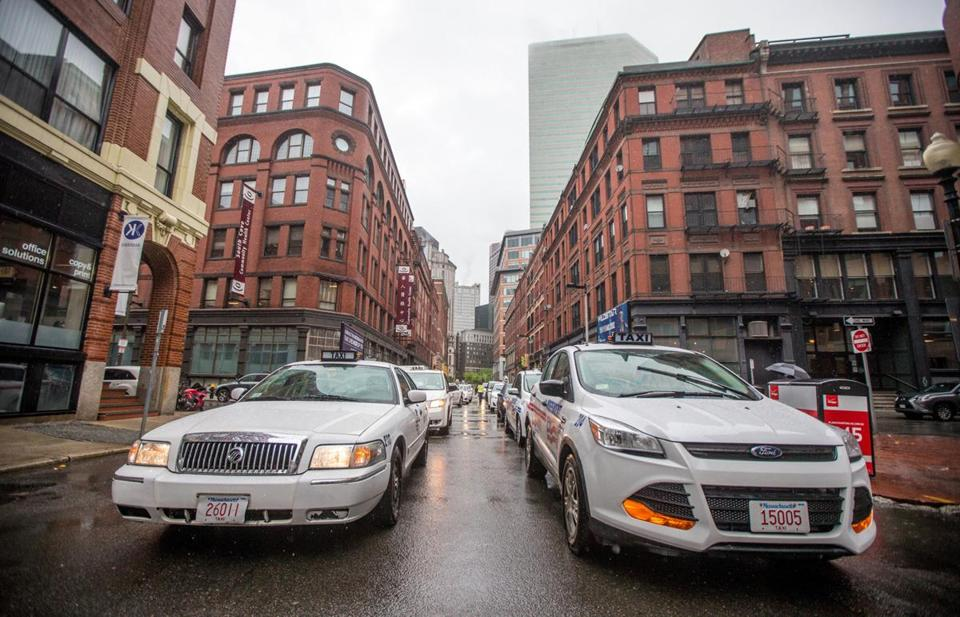 Hundreds of cabs honked their horns in protest in Boston in front of the Uber headquarters. (Aram Boghosian for The Boston Globe)