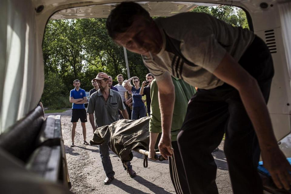 Men carried the body of a Ukrainian soldier killed in an ambush at a checkpoint in eastern Ukraine on  Thursday. More than 30 troops were injured in the attack.