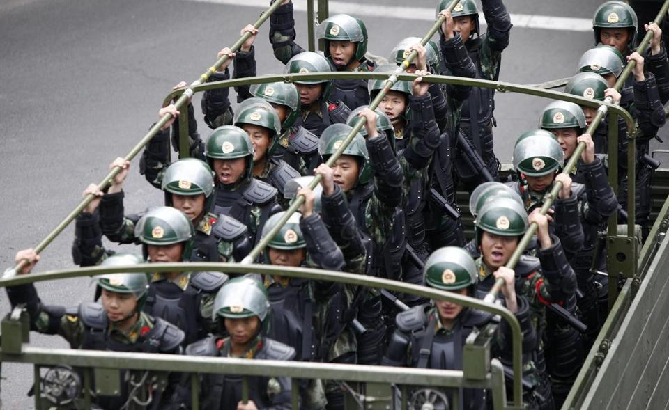 Paramilitary police officers traveled in a truck during an antiterrorism oath-taking rally in Urumqi, China.