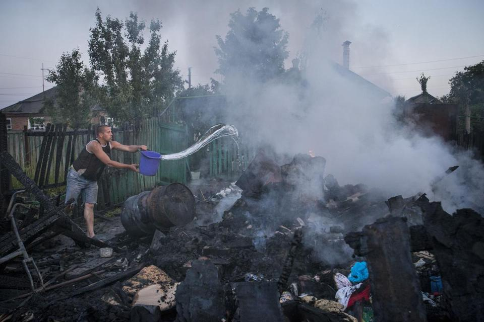 A Ukrainian sought to extinguish a fire Saturday in a shed destroyed by a mortar shell.