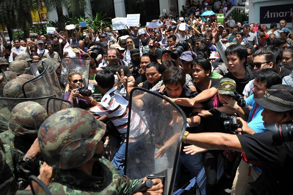 Protesters confronted soldiers in riot gear at an anti-coup rally in Bangkok, defying a martial law ban on public assembly.