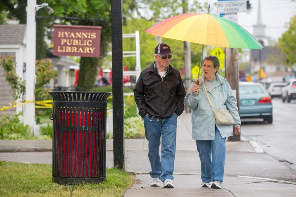 Locals Charlie Babineau (left) and Anita Babineau walk along on Main Street in Hyannis on Memorial Day.