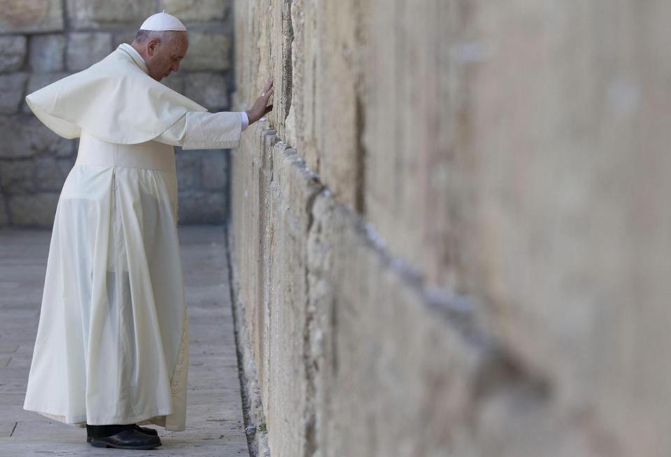 "Pope Francis bowed his head in prayer at the Western Wall in the Old City of Jerusalem. Before departing, the pontiff left in a crack in the wall a note written by hand in his native Spanish with the ""Our Father"" prayer."