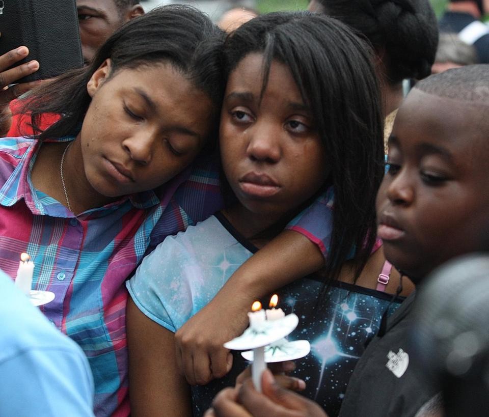 Emmanuela St. Louis ( center), a daughter of  Florence Beaulieu, was comforted by a cousin, Diana Paul, at the vigil.
