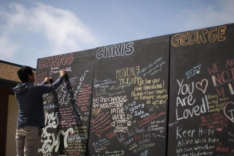 A student wrote chalk messages on a memorial wall for the victims of a killing spree at University of California, Santa Barbara.
