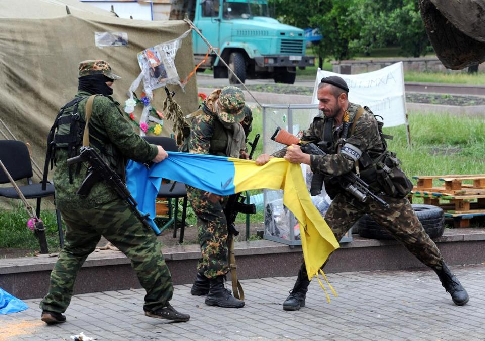 Pro-Russia fighters of the Vostok battalion ripped apart a Ukrainian flag outside a regional state building in the eastern city of Donetsk on Thursday.