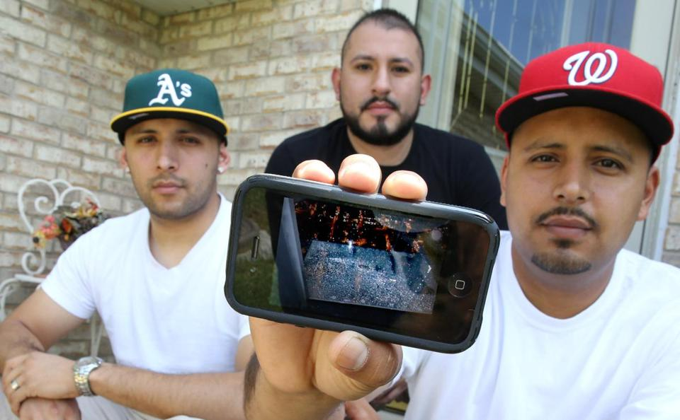 Ernesto Garibay, right, showed a photo of the cracks at Chicago's Willis Tower. He was with his brother Alejandro Garibay, left, and their cousin Antonio Saldana, center, when the cracks appeared Wednesday.