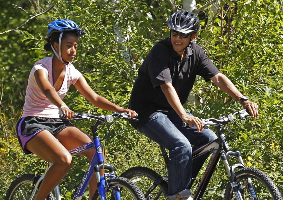 U.S. President Barack Obama rides alongside his daughter Malia during their family vacation on Martha's Vineyard in Massachusetts in this August 23, 2011 file photo. Both Obama and Republican Mitt Romney are likely to spend little of the summer in their vacation homes as the two campaigns strategize to shape their candidate's image. REUTERS/Kevin Lamarque/Files (UNITED STATES - Tags: POLITICS)
