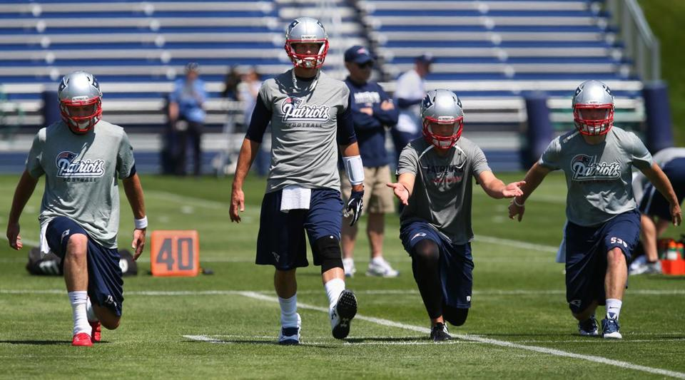 As always, Tom Brady stands just a little taller than everyone else as he leads a stretching exercise at Friday's OTAs in Foxborough.