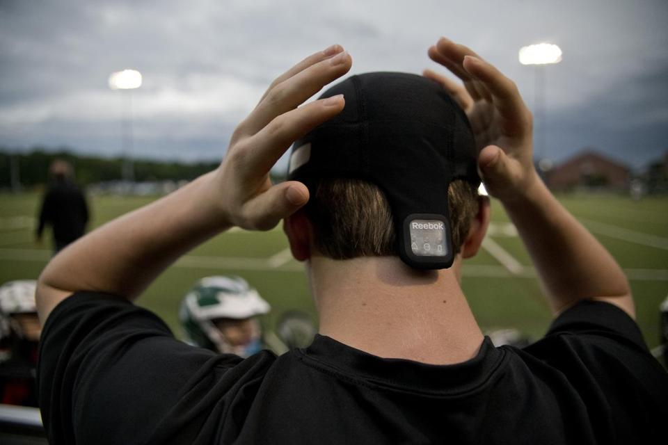 A Westwood Youth Lacrosse player adjusts a Checklight sensor, with its display panel visible above his neck,  before  putting on  his helmet.