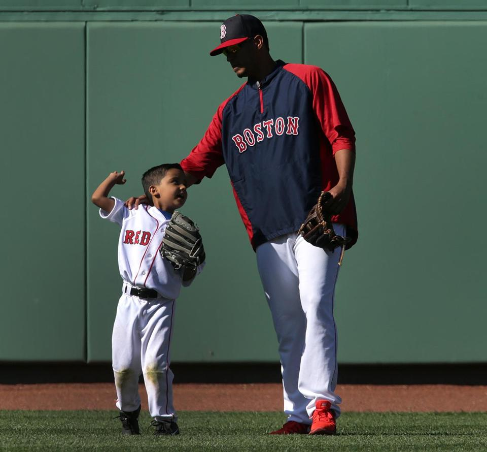 Red Sox pitcher Felix Doubront and his son enjoy some time on the field at Fenway Park prior to a recent game against the Tampa Bay Rays.