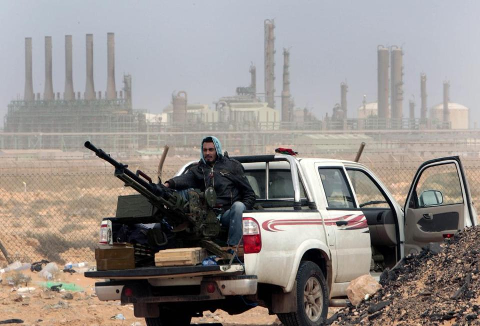 An anti-government fighter sits with an anti-aircraft weapon in front an oil refinery in eastern Libya in 2011.