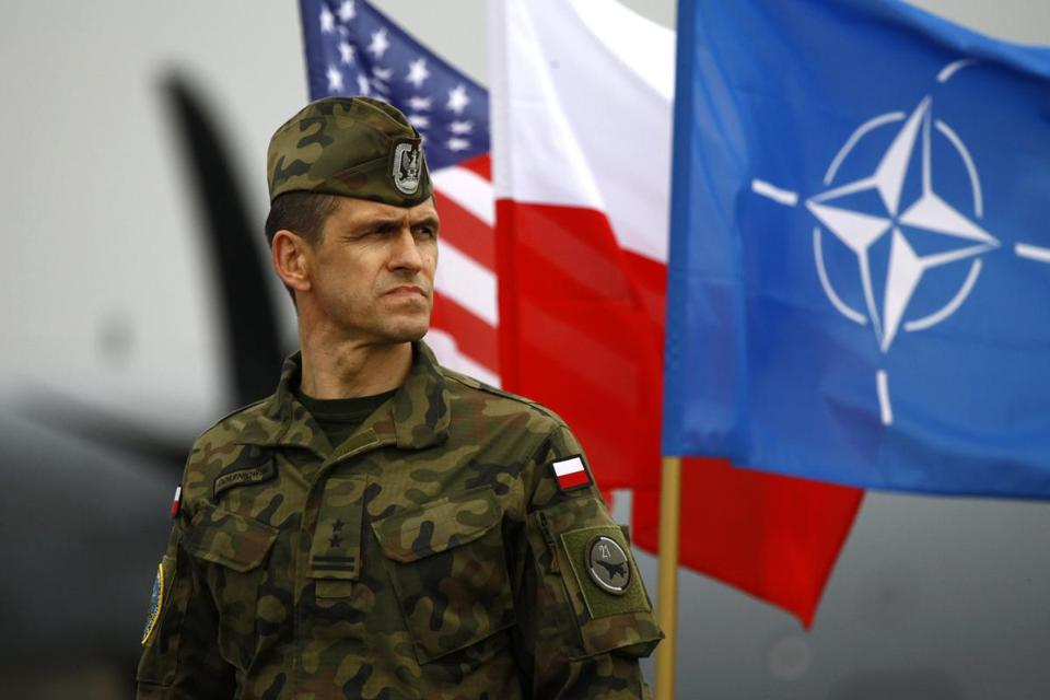 A Polish soldier stands near US, Poland, and NATO flags as US paratroopers arrive to participate in training exercises in April.