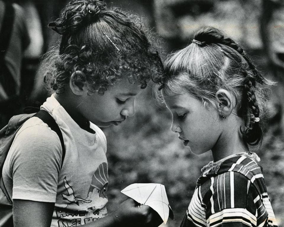 August 14 1980 / fromthearchive / Globe Staff photo by Ulrike Welsch / Clicia Cox, 8, (l) and Josephine Barreiro, 7, both of Boston, played the fortune teller question and answer folding paper game at Camp Ponkawissett. The camp was sponsored by several Boston community organizations and was a six-week program in Westwood's Hale Reservation.