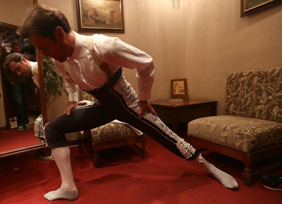 "Rafael de la Rosa, a ""bandillero"" for matador José María Manzanares's team, stretches while trying on his new clothes. De la Rosa, who is set to wear this suit the following week during Madrid's San Isidro festival, must stretch to make sure his movement isn't constricted by the fabric."