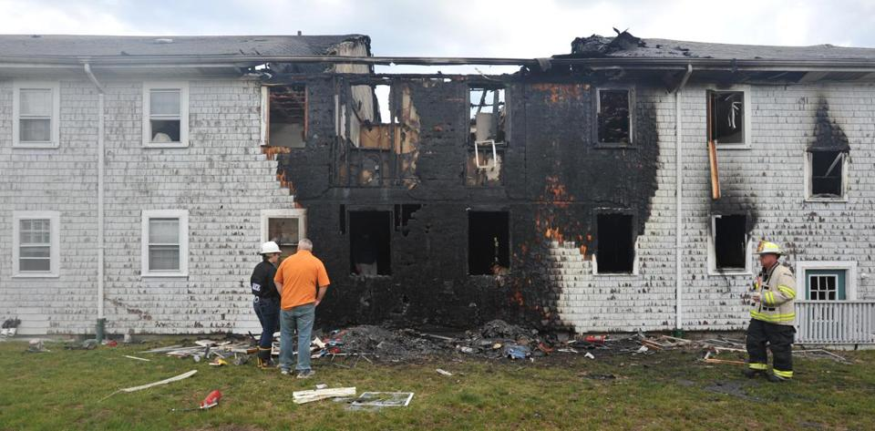 Firefighters inspected damages Friday from a blaze at a Dennis Port condo complex.