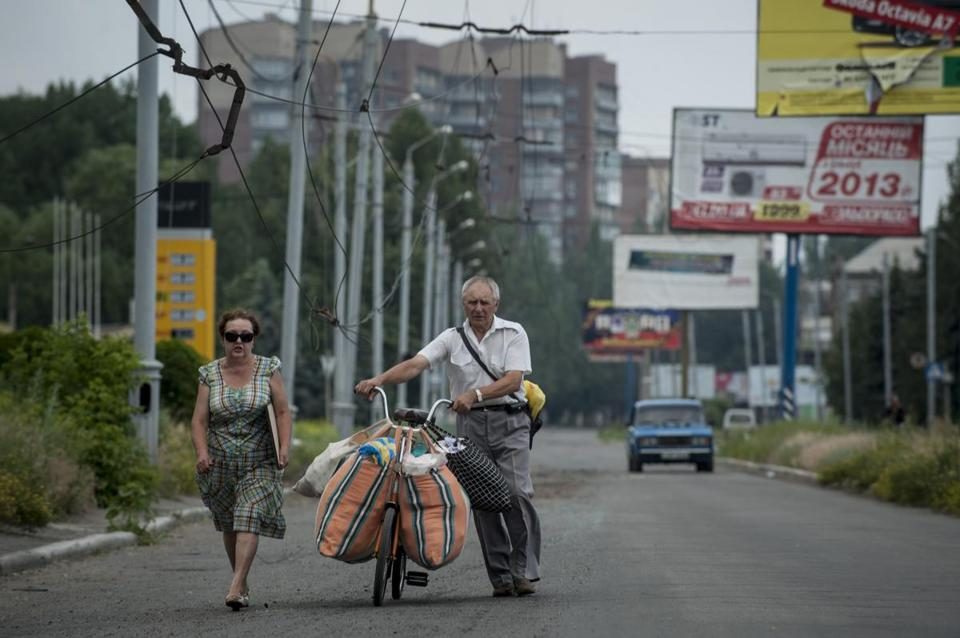 A Ukrainian family loaded their belongings on a bicycle and joined a growing number of residents fleeing  Slovyansk, Ukraine, amid escalating clashes.