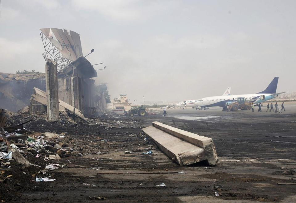 Remnants of a building damaged Sunday by Taliban mili-tants stood near planes at Jinnah International Airport.