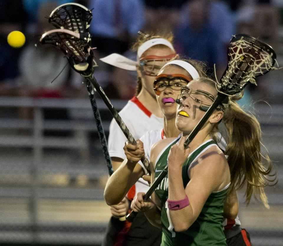 Westwood's Kasey Keane and North Andover 's Leah Chittick keeping their eyes on the ball during the MIAA Division 1 Girls Lacrosse Semi-Final game at Babson College on Monday.