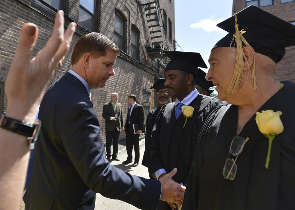 Mayor Martin J. Walsh shook the hand of Sam Bernard (right) as he made his way down the line of graduates at the Pine Street Inn homeless shelter Wednesday.