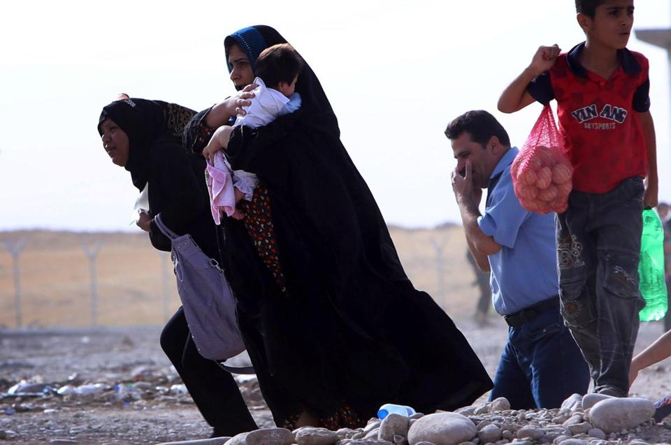 Iraqi families fleeing the violence in northern Nineveh province gathered Wednesday at a Kurdish checkpoint.