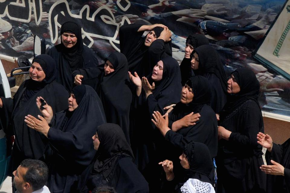 Mourners grieved Thursday near the coffin of a victim killed by a suicide bomber in Baghdad.