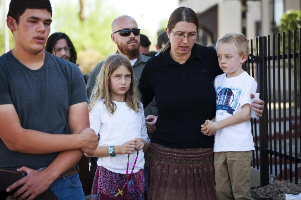 Parishioners prayed Thursday in downtown Phoenix at a Roman Catholic church where the Rev. Kenneth Walker, 28, was shot to death Wednesday night in what police described as a burglary. The Rev. Joseph Terra, who was badly injured, called 911 and administered last rites to his dying friend.