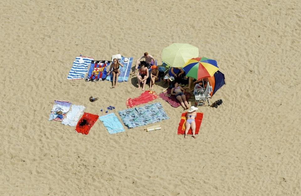 An aerial view of sunbathers on the beach in Noordwijk, the Netherlands, where the average work week is 29 hours.