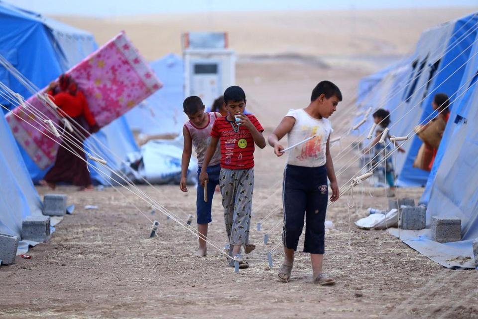 Refugees walked through a refugee camp outside Irbil, Iraq, on Thursday.
