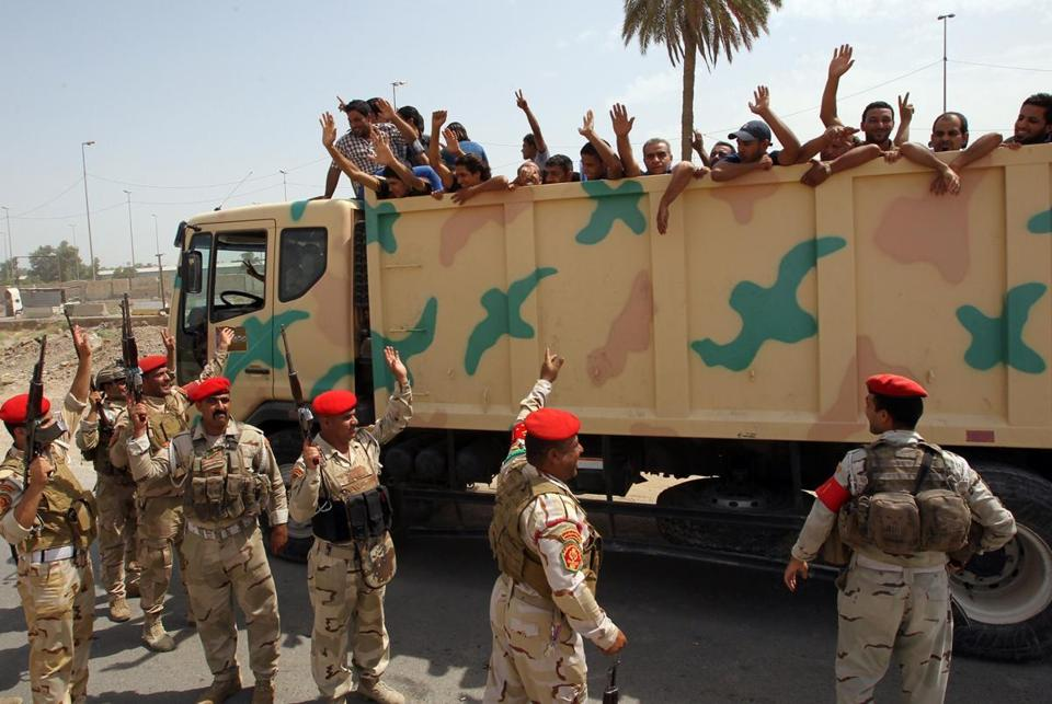 Iraqi men who volunteered to join the fight against a major offensive by militants in northern Iraq waved to soldiers from the back of an army truck Friday.
