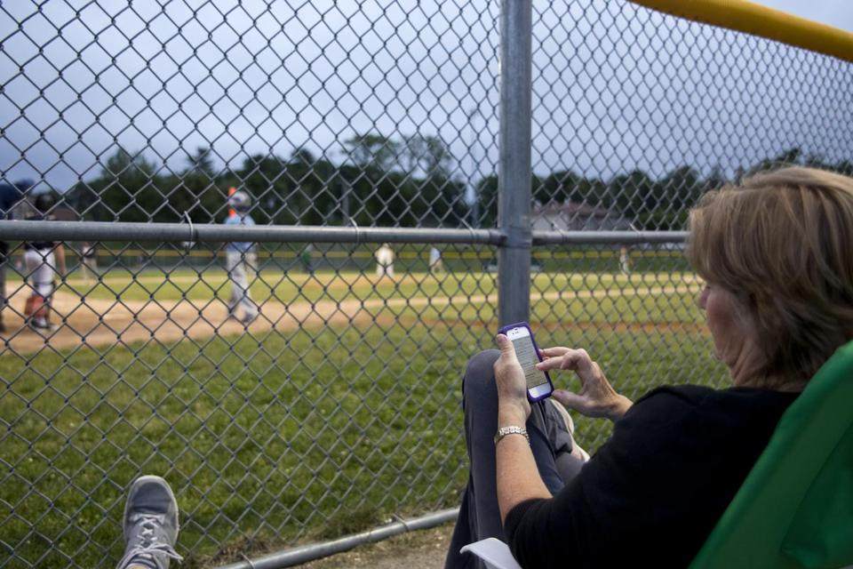 Patty Andresino caught up on her Facebook page while her son, Joe, played for Sullivan Insurance in the Milton Little League playoffs.