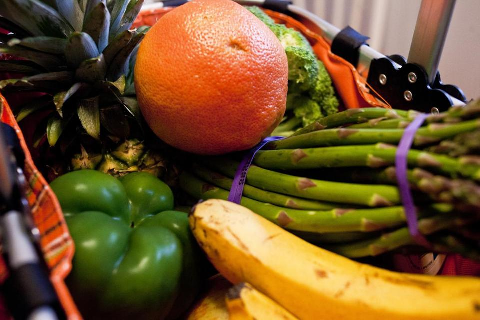 Fresh fruits and vegetables piled up in a grocery basket in Laura Smith's apartment.