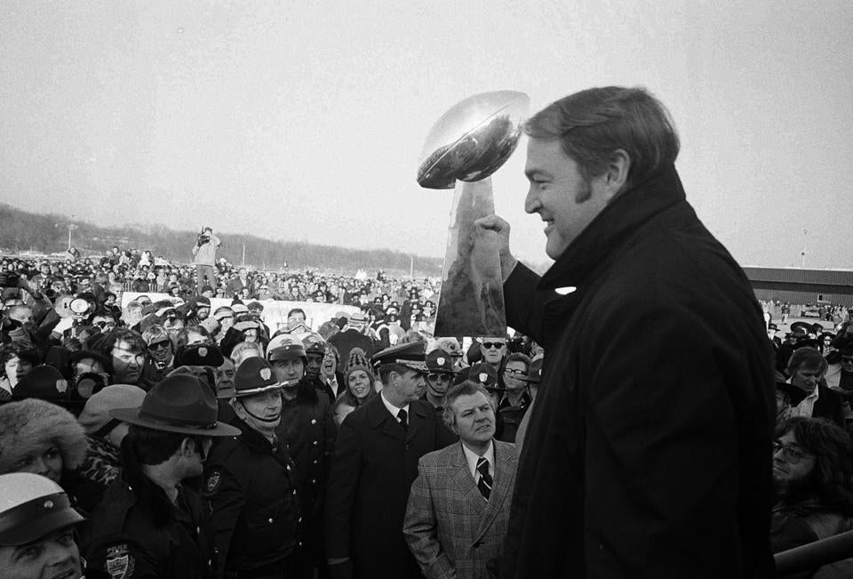 Steelers coach Chuck Noll held the Lombardi trophy aloft before fans who greeted the team at the airport. Noll is the only couch to have won four Super Bowls. He died Friday night at the age of 82.