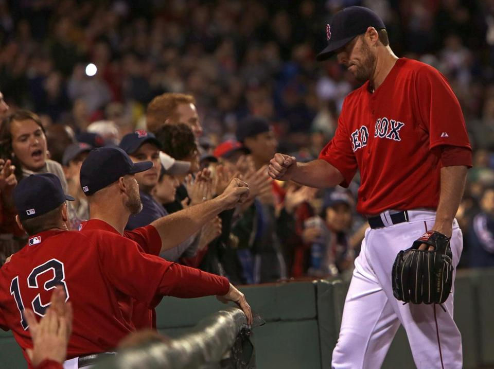 John Lackey is greeted by his teammates after being pulled from the game in the seventh inning. (Barry Chin/Globe Staff