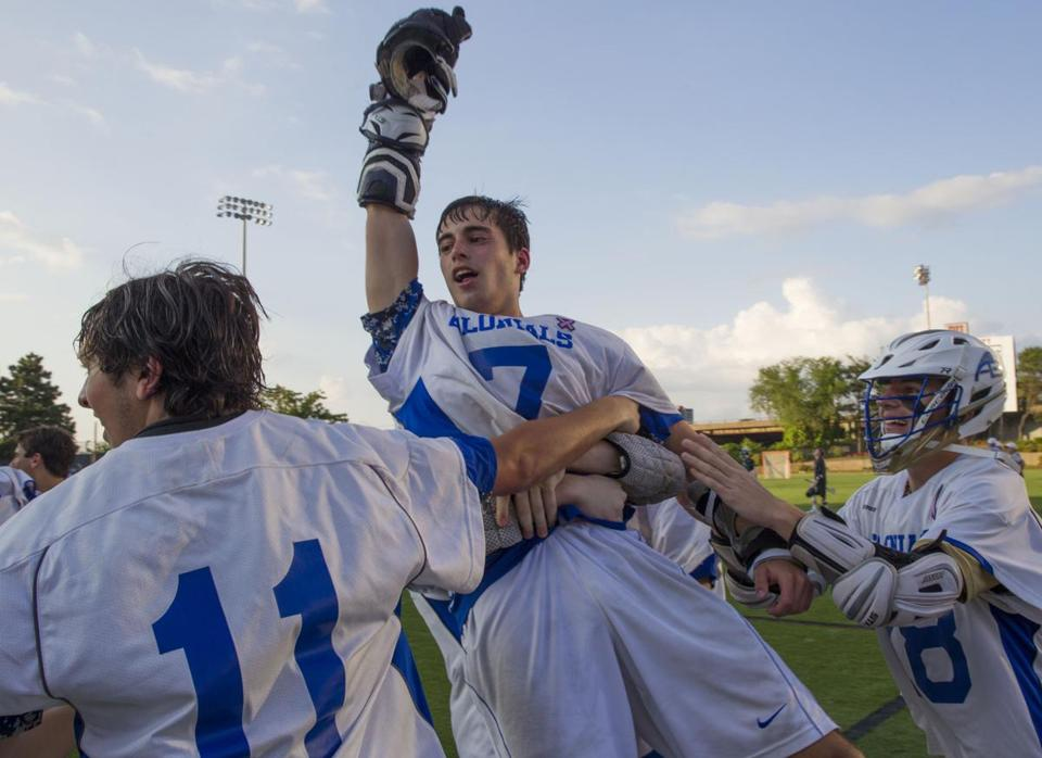 Christopher Wiggins is hoisted into the air by teammates after his goal in double overtime lifted Acton-Boxboro to a victory in the Division 1 state title game. (Jay Connor for the Globe).