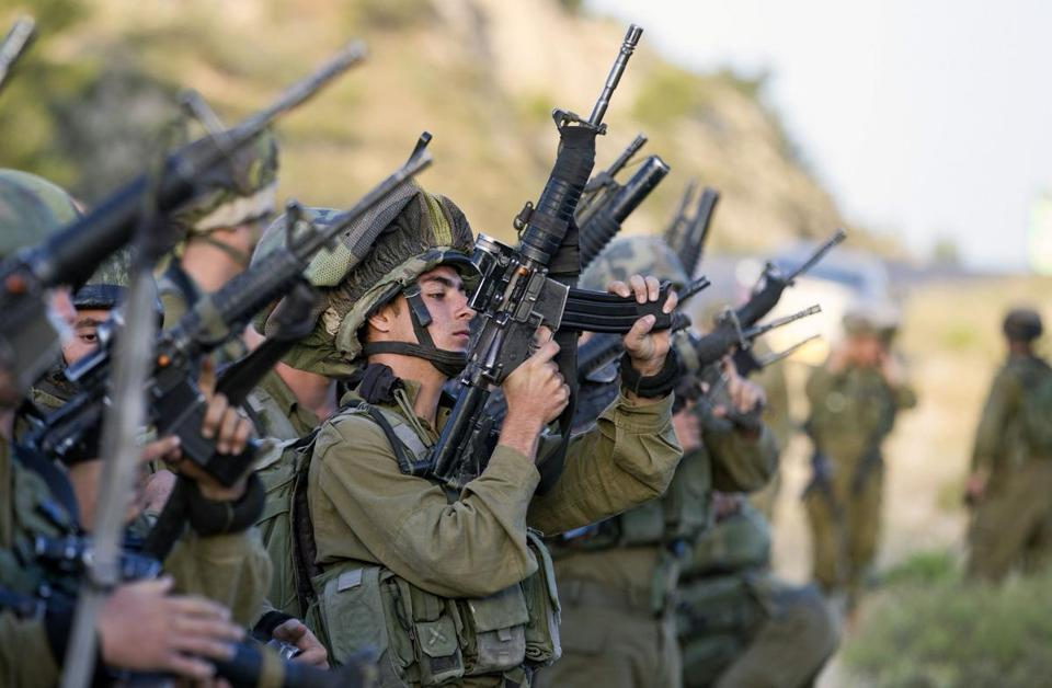 Israeli soldiers load their weapons during a search for three kidnapped Israeli teens.  Baz Ratner Photo/Reuters