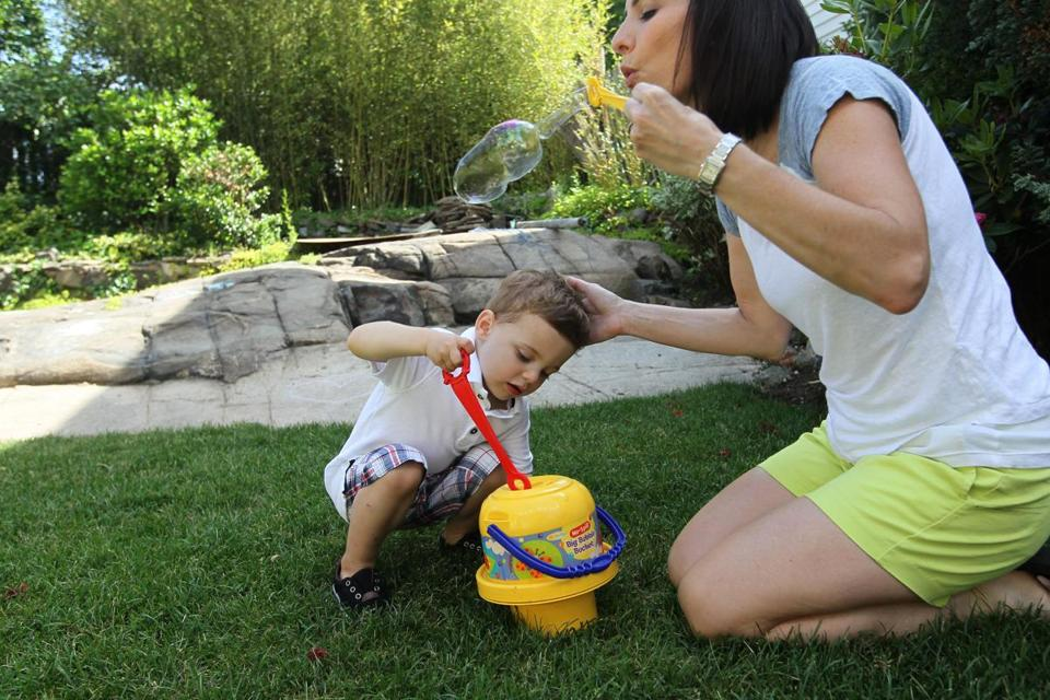 Kyle Donovan blows bubbles in her backyard with her 2-year-old son Matthew. She says she is often conflicted about wanting her son to have a sibling.