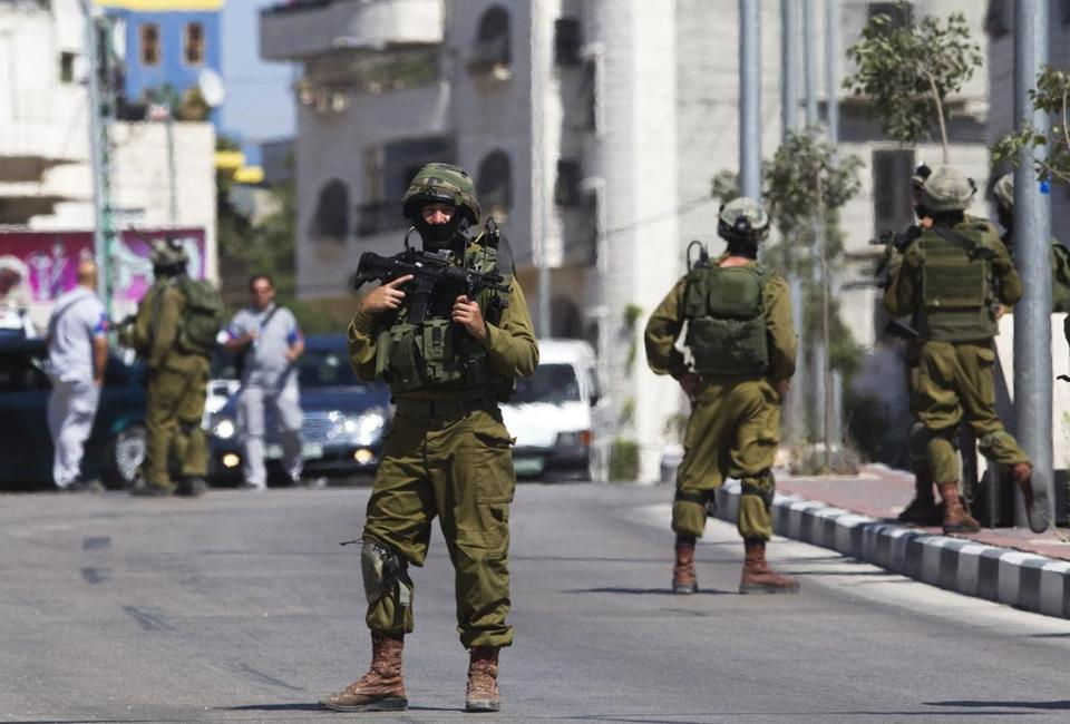 An Israeli soldier stood guard in the West Bank city of Hebron during an operation to locate three missing teenagers.