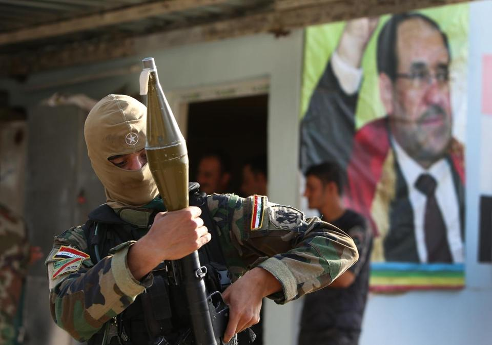 A Shi'ite gunman stood in front of a portrait of Iraq's prime minister, Nouri al-Maliki, in Kirkuk province on Friday.