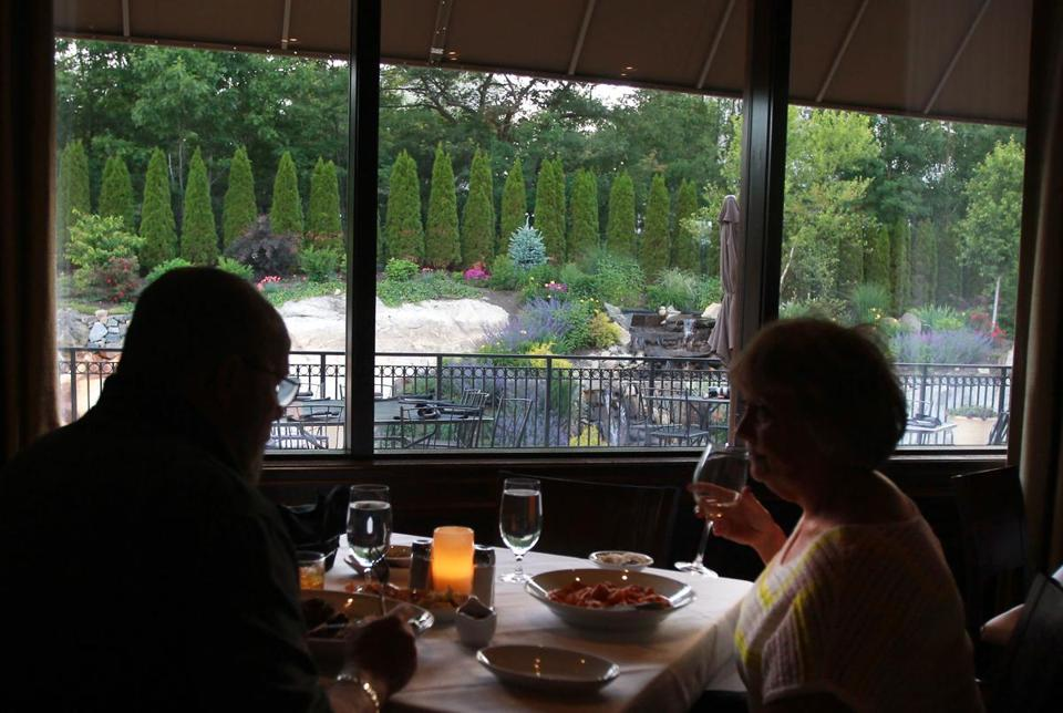 Diners inside Rosaria Steakhouse in Saugus look out at the patio and rock garden.