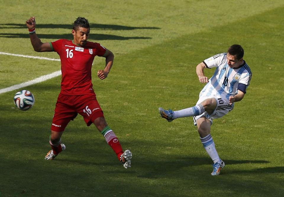 Iran's Reza Ghoochannejhad (left) is a step slow in stopping Argentina's Lionel Messi from getting off the winning goal.