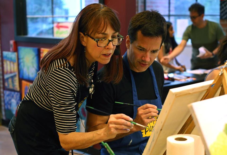 Longtime commercial artist Karin Samatis works with Eric Larson of Cambridge in a paint-and-sip class at Pinot's Palette in Lexington.